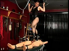 Mistress in leather and heels punishing slave boy